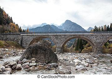 river in alpes under bridge