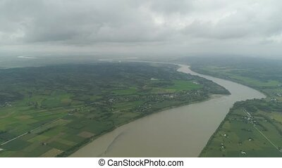 River in farmlands. Philippines, Luzon - River passing...
