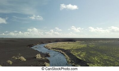 River in Iceland - River flowing through the black plains of...