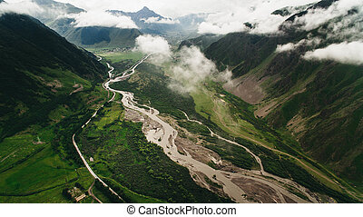 river in mountains with clouds