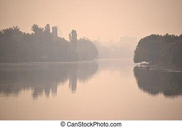 river in the fog at sunset sunrise