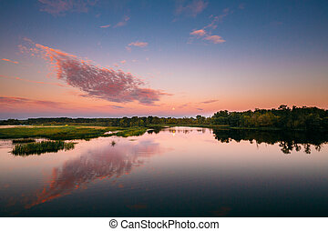 River Landscape In Belarus Or European Part Of Russia In Sunset Time Of Summer Evening. Moon Rising Over Water Lake Or River. Nature At Sunny Evening.