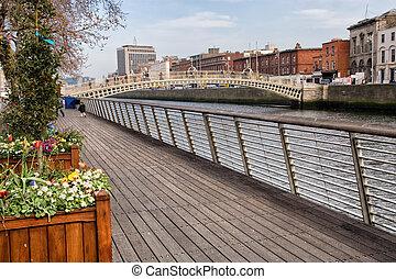 Boardwalk along river Liffey and Ha'penny Bridge in the city of Dublin, Ireland.
