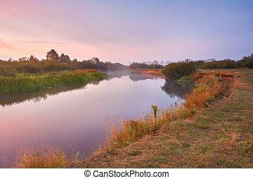River misty autumn sunrise. Colorful dawn. Cloudy sunrise.