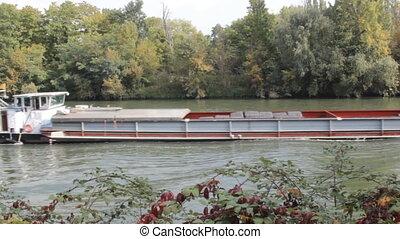 River navigation in France. Barge on Seine. cargo ships...