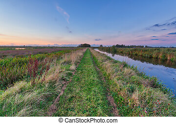 Path along river in Onlanden Nature reserve waterlogging area Groningen, Netherlands