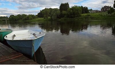 River pier with moored empty blue boat slow motion shot