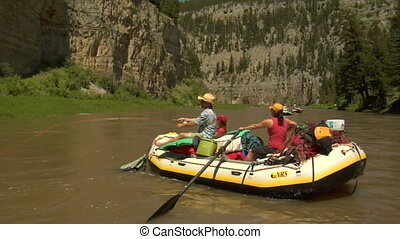 River rafts packed for camping with fisherman