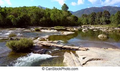 river rapids run under bridge on stones against green hills...
