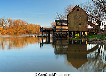 River reflection with watermill and tree
