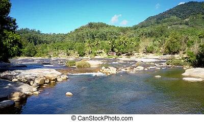 river runs among rocks against distant hills under blue sky