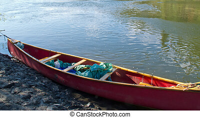 River shore and red canoe in green water
