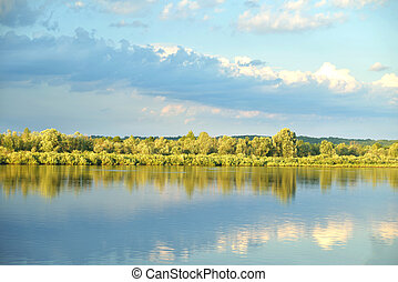 river, sky, clouds before the rain, summer sunlight, reflections of trees and sky in the water