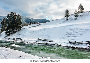 river through the village in winter - frozen river near the...