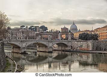 View of the bridge of Ponte Vittorio Emanuele II and saint Peters basilica over the river tiber. Rome, Italy.