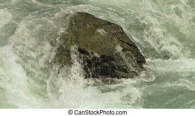River water crashing over a rock - Closeup steady shot of...