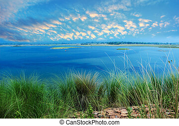 River with blue sky green grass landscape