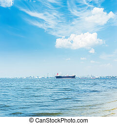 river with ship on horizon and white clouds in blue sky over it