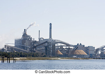 riverfront Florida paper mill with large wood chip storage pile