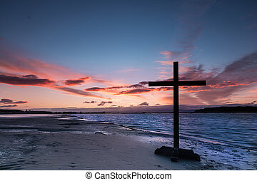 Riverside Dawn Cross - Black cross on a river beach at dawn....