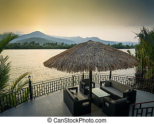 riverside sunset view in kampot cambodia asia with deck sofas