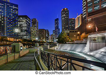 Floodlit Centennial Fountain and river side walk in Chicago at night