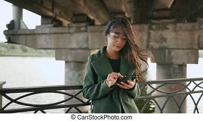 rivière, smartphone, délassant, jeune, asiatique, texting, femme, remblai
