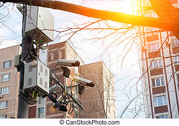 Road and lane tracking cameras hang over the roadway. Against the backdrop of urban high-rise buildings
