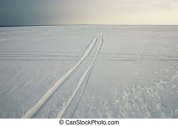 tracks on frozen snowcovered lake - road and tracks on ...