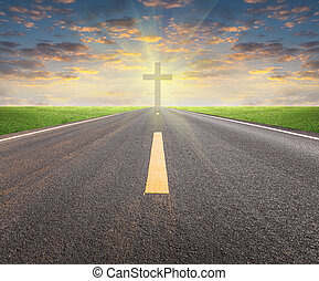 Asphalt road and crucifix with sky background.