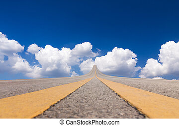 Road asphalt to the sky over the clouds
