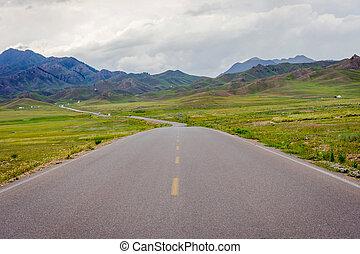 Road at Sayram Lake, China - Road thru the mountains at...