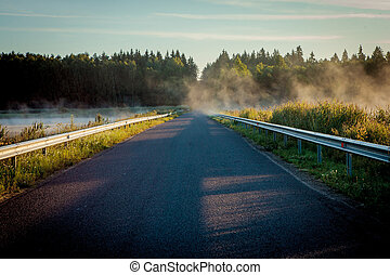 Road between two lakes in the misty