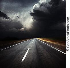 Road - Blurred asphalt road and dark thunder clouds over it