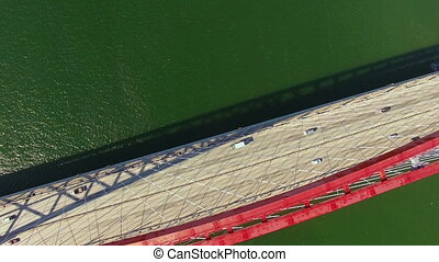 Road bridge river. Quadcopter flies over the bridge, view from above on the passing cars