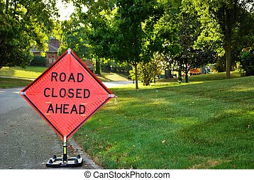 road closed ahead construction sign in a residential neighborhood