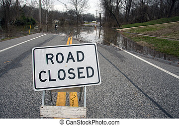 Road closed from flooding - A road closed sign in the middle...