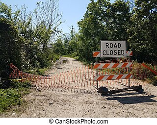 road closed sign and barricade and trail
