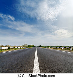 road closeup under cloudy blue sky