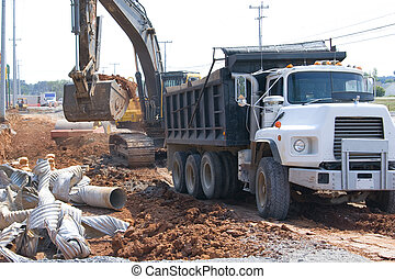 Dump truck being loaded with dirt and old drainage pipe, to be hauled to landfill