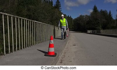 Road construction worker collect road signs