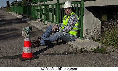 Road construction worker sitting and using tablet PC on the bridge