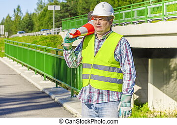 Road construction worker with traffic cone