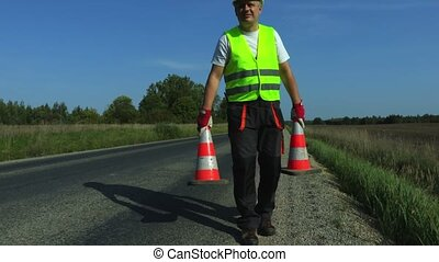 Road construction worker with two traffic cone