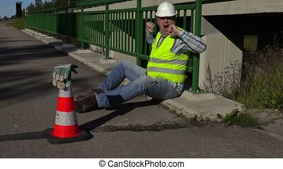 Road construction worker yawns on the bridge