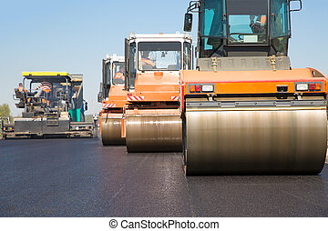 Road rollers with tracked paver machine during road construction
