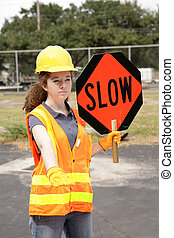Road Crew Slow Sign - A female construction road crew member...