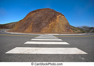Road curves around a hill of rocks - A sharp curve in a road...