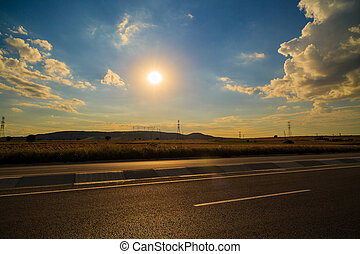 road in a field at sunset