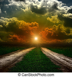 Road in field with stormy clouds and sun